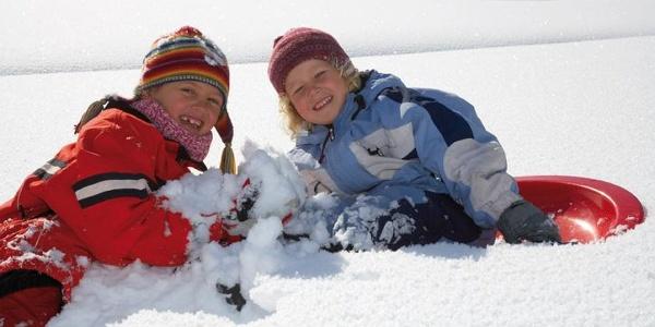 Kinder tollen im Schnee.