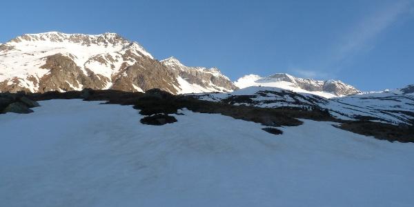 In der Sonne erstrahlen bereits die hohen Berggipfel. Ganz hinten ragt der Turnerkamp empor.