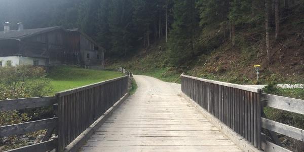Über die Brücke und dann links hinter dem Haus vorbei, unmittelbar danach rechts in den Wald hinauf.