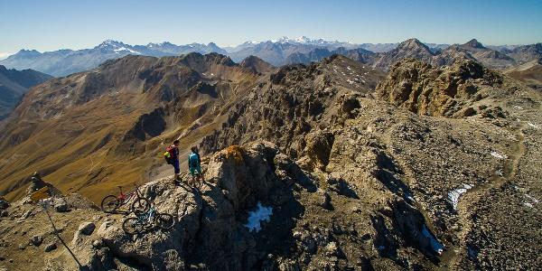 Zwei Mountainbiker geniessen Aussicht auf dem Piz Umbrail