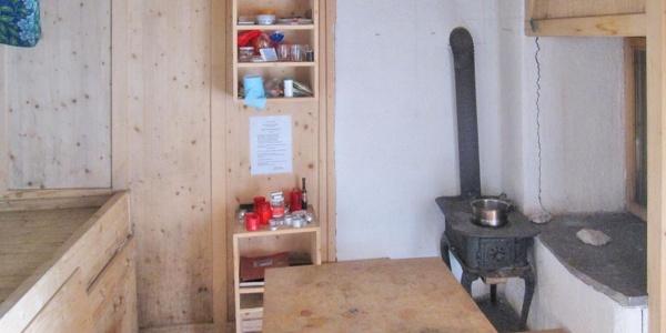 Innenraum der Linderhütte mit Schlafplatz, Kochstelle (Ofen) und Sitzgelegenheit