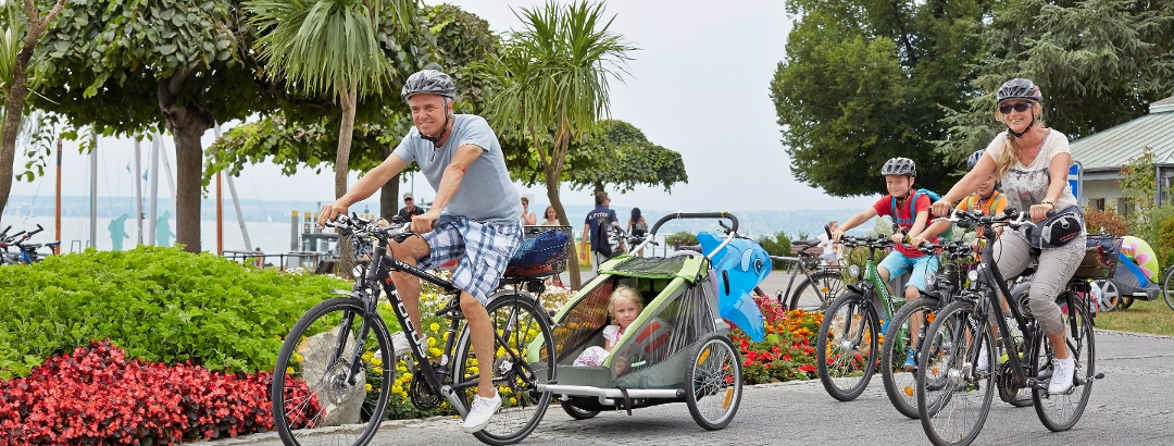 Familie beim Radfahren an der Schiffsanlegestelle Hagnau