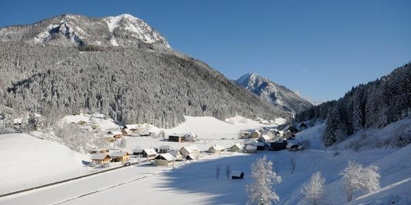 Zell Pfarre im Winterkleid mit Freiberg (li.) und Hochobir