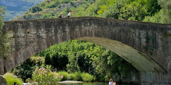 Il ponte romano a Ceniga con la piccola spiaggia sul fiume