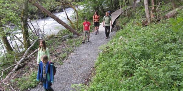 Familie wandert dem Wildbach Seez entlang.