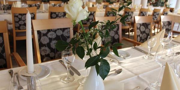 Weiße Rose auf gedecktem Tisch