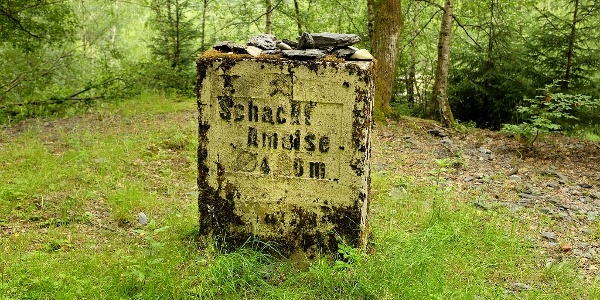 "Der Betonblock markiert den Schacht der alten Eisenerzgrube ""Ameise"" direkt am Wegesrand"