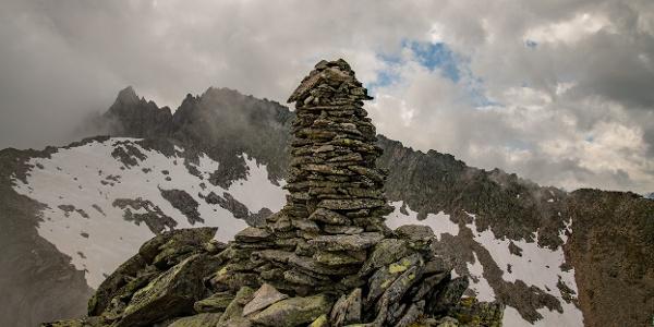 Ein Steinmanderl auf dem Gipfel - im Hintergrund die Mittlere Grinbergspittze