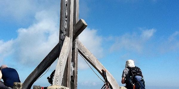 Das hölzerne Gipfelkreuz auf massiven Mauern.