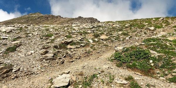 Die letzten Meter zum Gipfelkreuz in schrofigem Gelände.