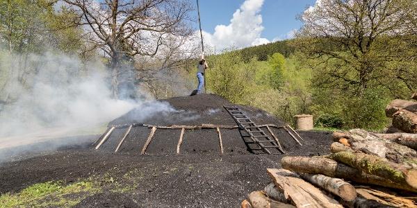 Köhler bei der Arbeit am schwelenden Kohlenmeiler