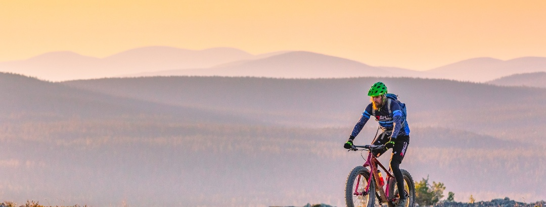 Maastopyöräilijä aurigonlaskiessa Kukastunturin huipulla, Pallastunturit taustalla