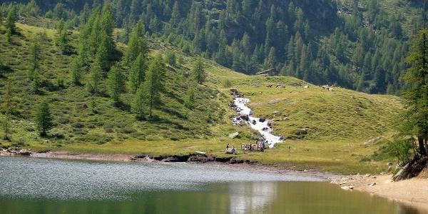 Der Fischersee mit seinem flachen Uferzugang liegt unmittelbar neben/ unter der Mittleren Weißbrunnalm (im Bild ist die Hütte erkennbar) und ist nach dem Weißbrunnsee am Wanderbeginn der zweite See, den wir erreichen.