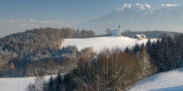Kirche und Wirtshaus vor Bergkulissee: Johannishögl in Piding im Winter
