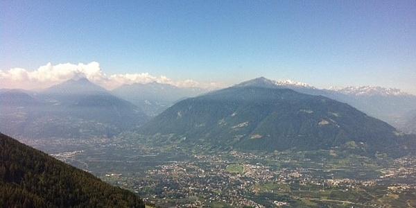 Grandioser Ausblick hinunter auf die Kurstadt Meran, die kleine und große Laugenspitze (links), das Vigiljoch (Bildmitte), die eis- und schneebedeckten Gipfel der Ortlergruppe am Horizont und den Eingang ins Vinschgau (ganz rechts)