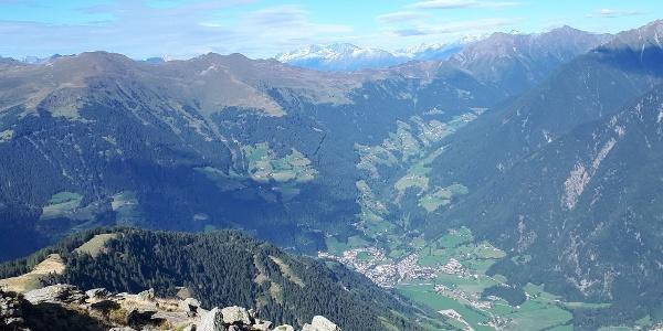 Grandioser Ausblick hinunter ins Passeiertal auf das Dorf St. Leonhard in Passeier, das Waltental, den Jaufenpass und die schneebedeckten Pfitscher Berge im Hintergrund