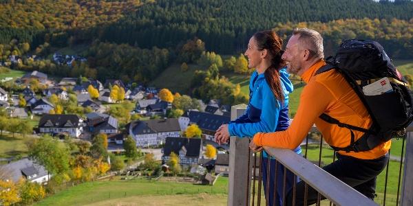 Zwei Rothaarsteig-Wanderer schauen auf das herbstliche Niedersorpe