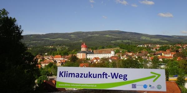 Klimazukunft-Weg: Wegweiser im Hintergrund Schloss und Pfarrkirche Pöllau