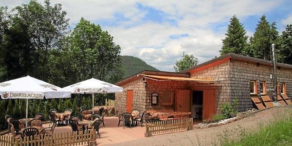 Die Schankhütte von außen mit Terrasse