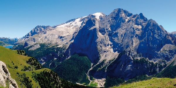 Die eingeschneite Spitze der Marmolada und im Vordergrund der felsige Gran Vernel. Links sieht man den Fedaia-See