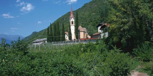 Burgstall bei Meran, bei der Kirche führt die Wanderung durch schattigen Wald Richtung Vöraner Seilbahn-Talstation.