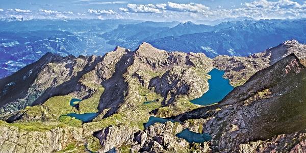 Die Spronser Seen aus der Vogelperspektive. Dahinter das Etschtal und am Horizont die Dolomiten.