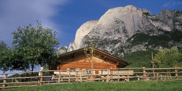 Die Hütte der Tuff Alm unter den Felswänden des Schlerns.