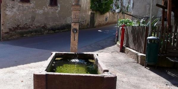 Am Dorfbrunnen in Pigeno im Überetsch vorbei.