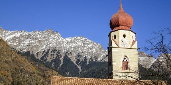 Der Kirchturm der Pfarrkirche Partschins mit der Texelgruppe im Hintergrund.