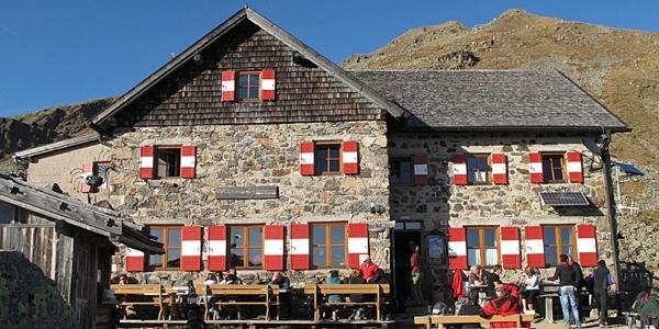 Die steinerne Fassade des Schutzhauses schmiegt sich beinahe farbgleich in das massiven Grau der Berglandschaft.