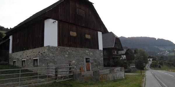 Historische Gebäude stehen entlang des Weges kurz nach Arriach