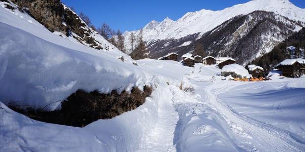 Sur le chemin de randonnée hivernale direction Furi, hameau de Blatten en arrière-plan