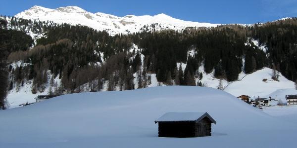 Romantische Hütten säumen den Weg über die Wiesen. Im Hintergrund Rötenspitze und Muttenkopf.